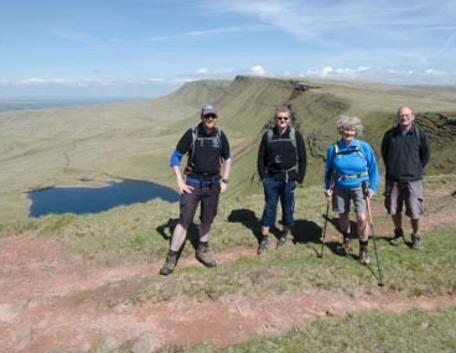 Your guide James Cresswell and a walkign group with Llyn Fan Fach behind.